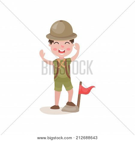 Cute little child standing with one foot on stone near flag and cheerfully waving his hands. Cartoon boy scout character. Camping and adventure. Flat vector illustration isolated on white background.