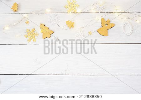 Christmas background on a white wooden background with a gold angel and a Christmas tree and a garland, top view.