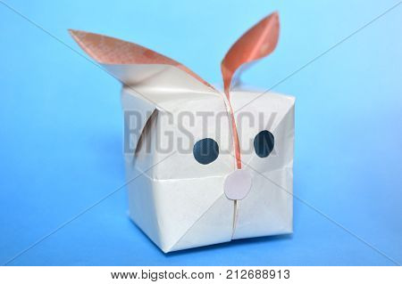 Origami balloon rabbit, paper folding, on blue background