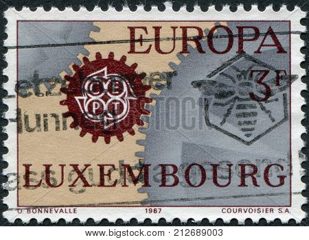 LUXEMBOURG - CIRCA 1967: A stamp printed in Luxembourg shows Cogwheels and emblem CEPT circa 1967