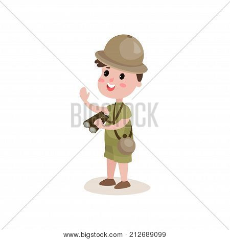 Smiling boy scout character standing with binoculars in hand isolated on white. Kid dressed in khaki shorts, t-shirt and hat. Scouting and terrain orientation concept. Cartoon flat vector illustration