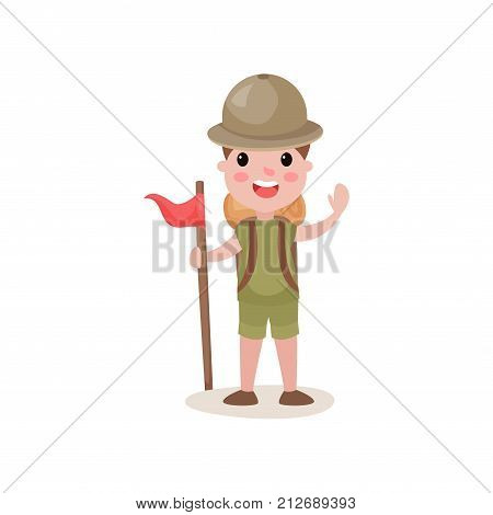 Kid standing isolated on white background with red flag and waving hand. Cartoon boy scout character in khaki garment with backpack on his back. Children s active recreation. Flat vector illustration.