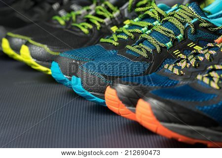 Three pairs of colourful running shoes / exercise trainers lined up in a row on a gym floor with potential text / writing space