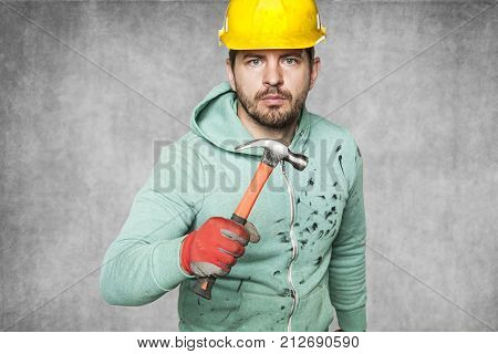 A Dangerous Worker Is Holding A Hammer In His Hand