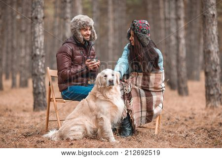 A guy with a girl is sitting on chairs with a dog in the autumn forest. The guy drinks a hot drink and the girl strokes the dog