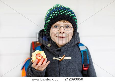 Little kid boy with eye glasses on the way to the school and eating fresh apple. Child with missing front teeth wearing warm clothes, glasses and backpack. Happy student or people. Education concept