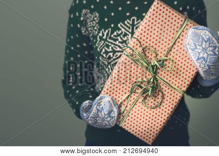 Christmas background. A girl in a New Year's sweater holds a present. Gifts for men. Merry Christmas. Gift for a girl. Sweater with Christmas ornament. Knitted dress. Box with gifts. Toned image.