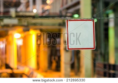 Blank white sign in red frame hanging on chains in the production