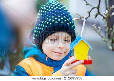 Little kid boy feeding birds in winter. Child hanging colorful selfmade bird house on tree on frosty cold day. Happy preschooler in colorful wam clothes. Selective focus on child and feeder with seeds
