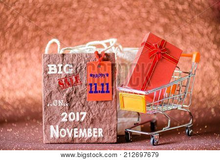 Soft focus mini shopping cart and shopping bags with label tags China 11.11 single day sale concept.