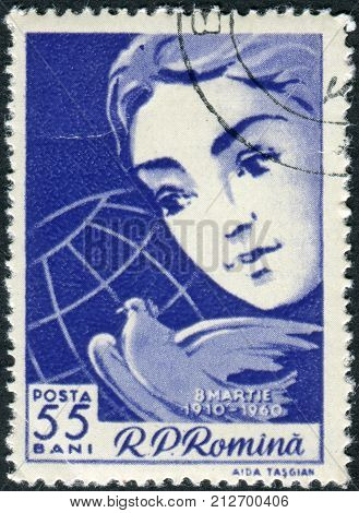 ROMANIA - CIRCA 1960: Postage stamp printed in Romania dedicated to the 50th anniversary of International Women's Day shows Woman's face peace dove and globe circa 1960