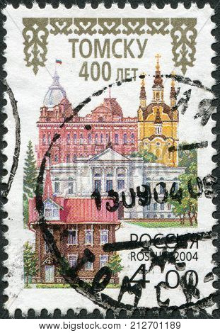 RUSSIA - CIRCA 2004: A stamp printed in Russia dedicated to the 400th anniversary of Tomsk shows the city administration Church of the Resurrection Tomsk State University a monument of wooden architecture circa 2004