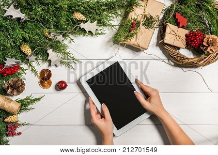Tablet computer in the human hands. Near the table with tablet computer gift box, christmas bell and fluffy fir branches. Free space for text. top view. Copy space. Closeup