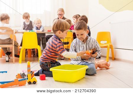 Two cute little boys playing with toy railway in kindergarten