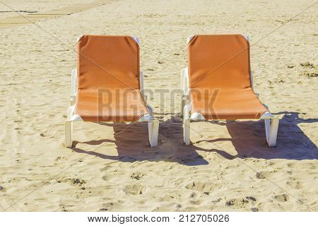 Two empty chaise lounges on the sand of the beach.