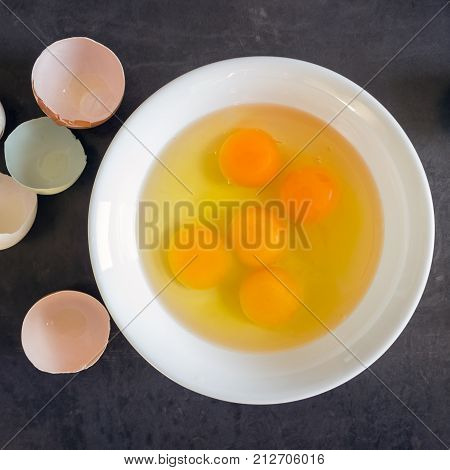Fresh eggs in a white bowl. Concept of organic products. Farm. Broken eggs with bright yolks.