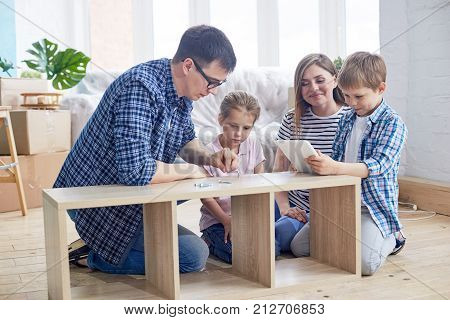 Loving young family of four gathered together at living room of new apartment and wrapped up in assembling wardrobe, pile of moving boxes on background
