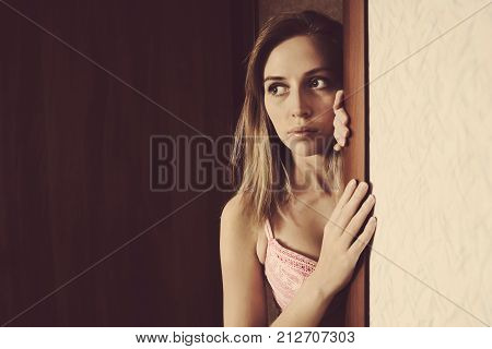 Beautiful Girl Peeks Peeking Out Of Doorway.