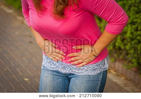 Young woman with menstrual pain, menstrual cramps, stomach pain, sharp abdominal pain. Strong stomach ache stock image.