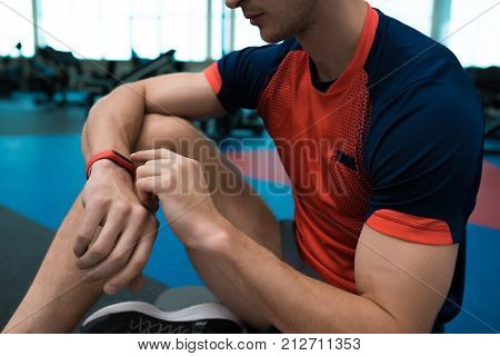 Mid-section portrait of unrecognizable modern sportsman checking fitness activity tracker sitting on floor in gym poster