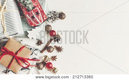Christmas Flat Lay. Wrapped Presents With Ornaments  Car Toy And Pine Cones Anise On Rustic White Wo