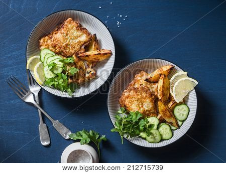 Two bowls with deep-fried fish and garlic baked potatoes on a blue background top view. Fish and chips. Flat lay