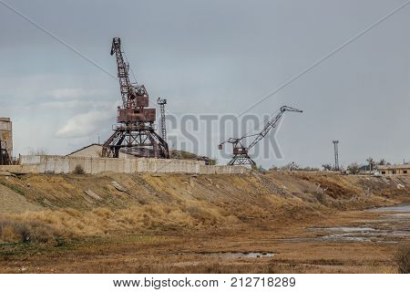Consequences of Aral sea ecological catastrophe. Abandoned port with rusty cranes on the shore of dried Aral sea.