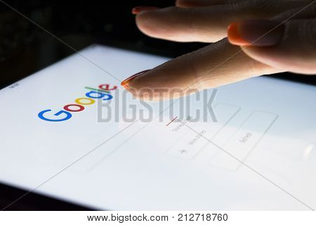 Sankt-Petersburg Russia November 8 2017: A woman's hand is touching screen on tablet computer iPad Pro at night for searching on Google search engine. Google is the most popular Internet search engine in the world.