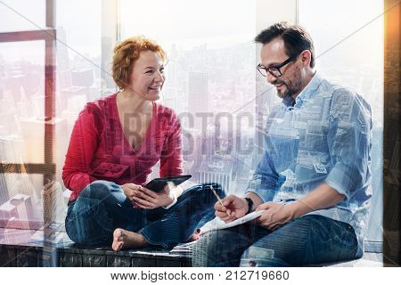 Cozy ambience. Pleasant cheerful couple sitting on the window sill and talking to each other while working