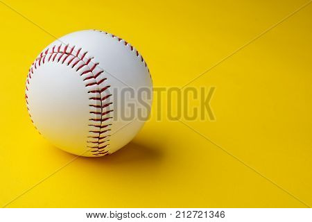 Baseball ball on yellow background with copy space.