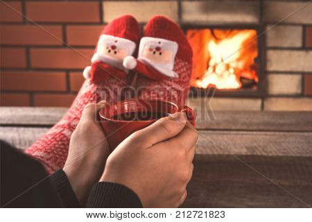 Teen's Hands Hold A Red Cup Of Coffee In Front Of The Fireplace. Christmas Holiday.