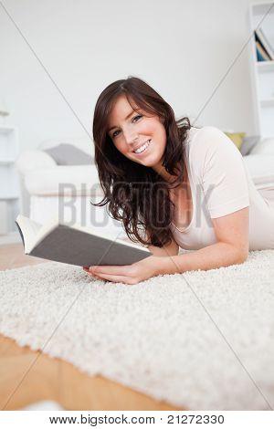 4Young attraktive Frau ein Buch zu lesen, beim liegen auf einem Teppich