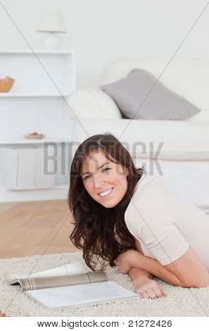 Junge Good Looking Frau eine Zeitschrift lesen, beim liegen auf einem Teppich