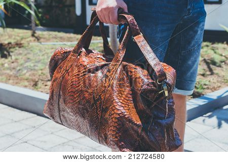 Young handsome man with luxury snakeskin python travel bag. Bali island.