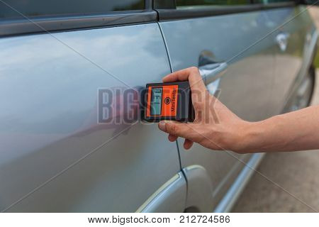 checking the body and doors of the car, the man measures the car's body with the appliance, car painting quality control