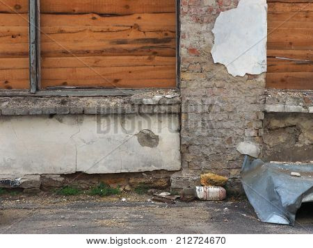 The Old Destroyed Brick Fence With Shields Of Wooden Slats Is A Warm Brown Color, Near The Fence Rag