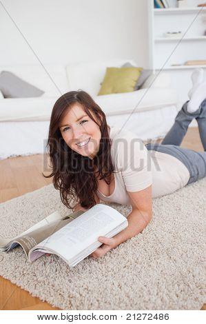 Charmante Frau, die eine Zeitschrift lesen, beim liegen auf einem Teppich