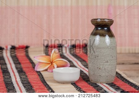 vintage sake bottle and small cup on wood