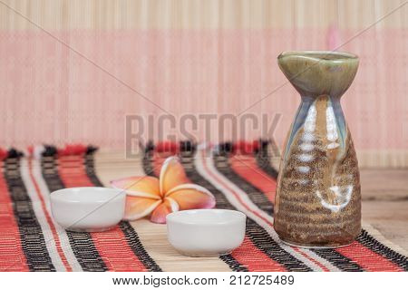 vintage sake bottle with small cup on table
