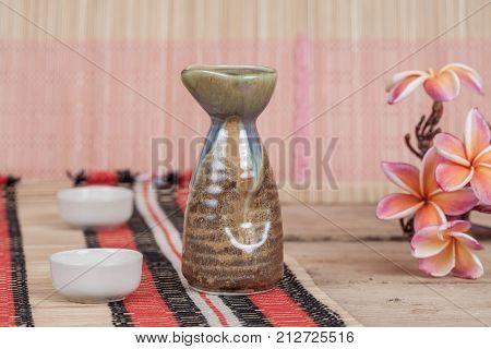 vintage sake bottle with fresh pink Plumeria flower on wood table