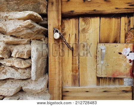Wooden door from the new brown natural board adjoins the ancient stone wall built of boulders and is closed on a padlock with a chain a fragment of a Tibetan house.