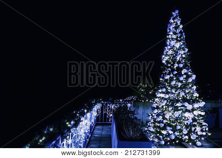 Ornate and lighted Christmas tree in the garden. Xmas tree and lighting of the house at Christmas time