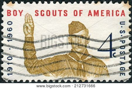 USA - CIRCA 1960: A postage stamp printed in the USA dedicated to the 50th Anniversary Boy Scouts of America shows Boy Scout Giving Scout Sign circa 1960