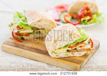 Ciabatta Sandwich with cheese on cutting board