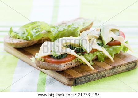 close-up of open sandwiches with avocado, cheese,salad leaves and tomatoes on cutting board