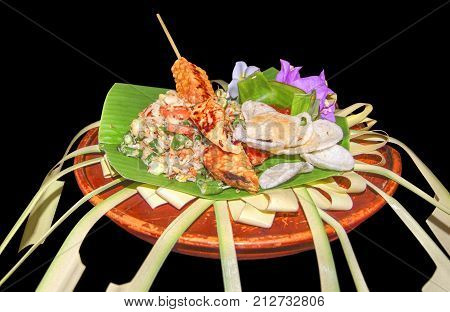 ornamented colorful indonesian dish in black back