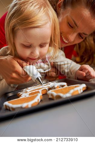 Mother And Baby Decorating Homemade Christmas Cookies With Glaze