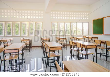 Lecture room or School empty classroom with desks and chair iron wood for studying lessons in high school thailand interior of secondary education with whiteboard vintage tone educational concept