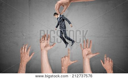 A giant hand holds a small businessman over many giant grabbing hands on concrete background. Business and competition. Corporate rivalry. Professional candidates.