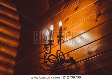 looks like a candle iron-shod antique lamp on the cement textured wall